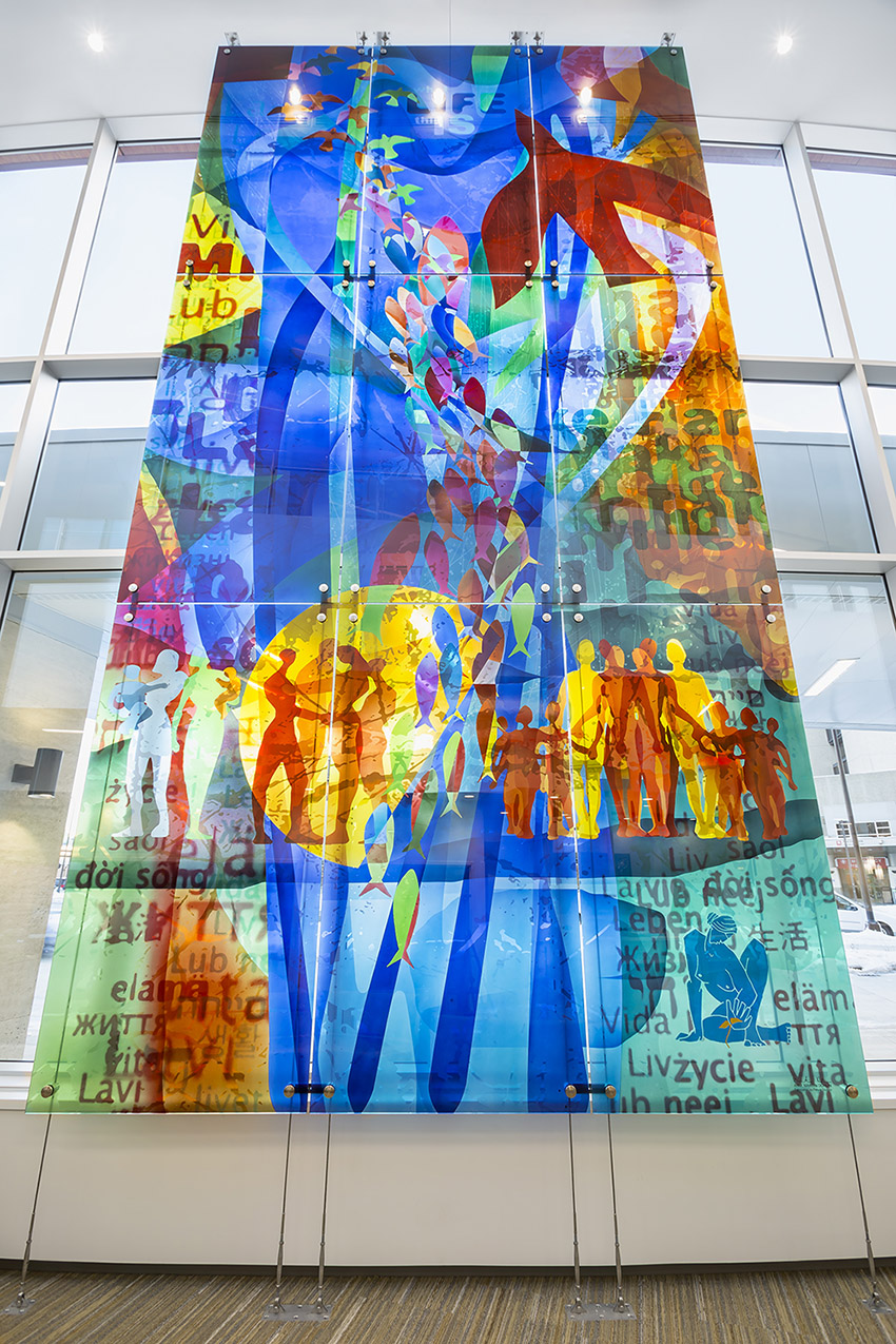 A tall panel of glass art is installed in window of healthcare facility